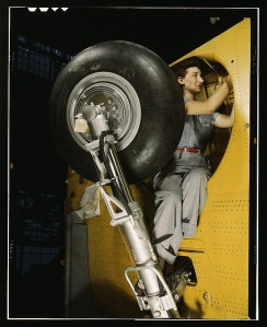 """This woman is working inside a wheel well, at Vultee-Nashville. She is working on a """"Vengeance"""" diver bomber. From the Library of Congress WWII Color Photograph collection.Photographer: Alfred T. Palmer"""